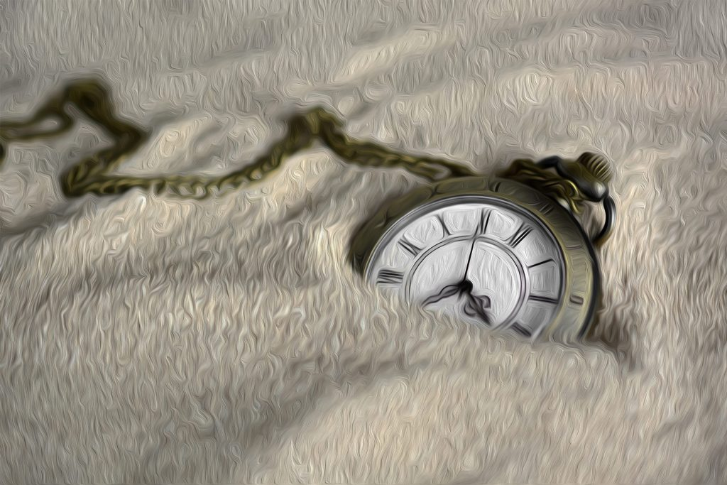 image of a pocket watch being buried by the sand of time illustrating the fleeting nature of life